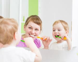 Mother and child practicing healthy dental care